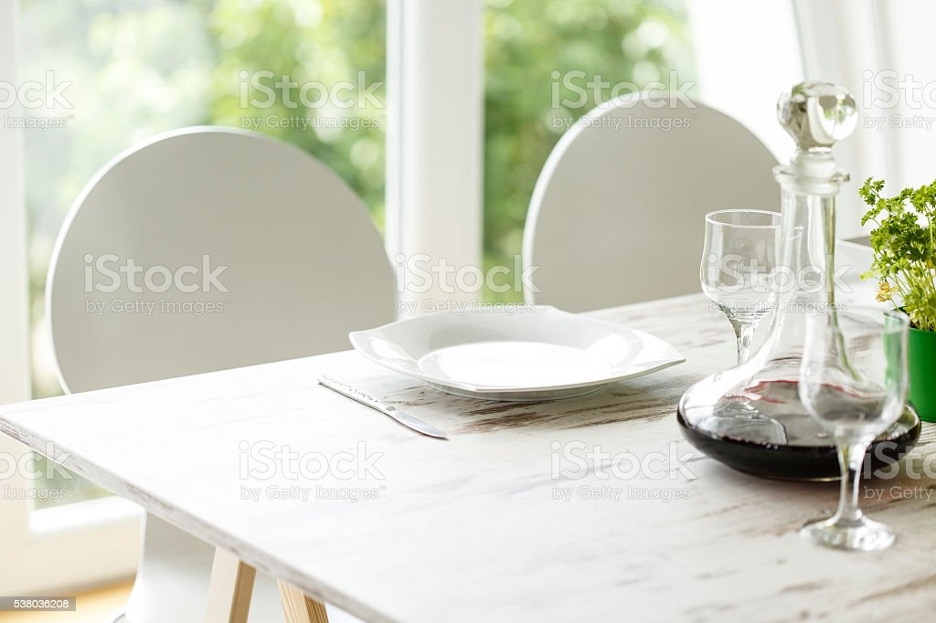 Empty plate and bottle of red wine on dining table stock photo