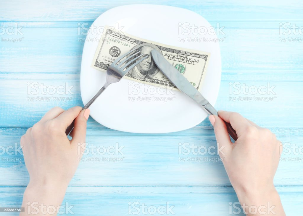 empty plate cutlery in hands concept we eat money business stock photo