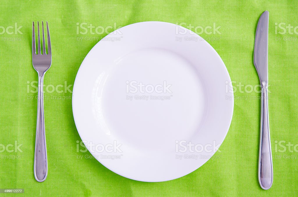 Empty plate, fork and knife on green background stock photo