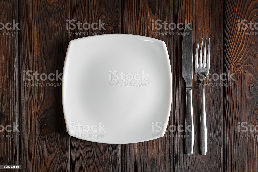 Empty plate, fork and knife on the dark wood background stock photo