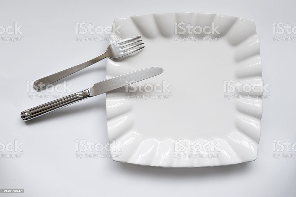 Empty plate, fork and table knife stock photo