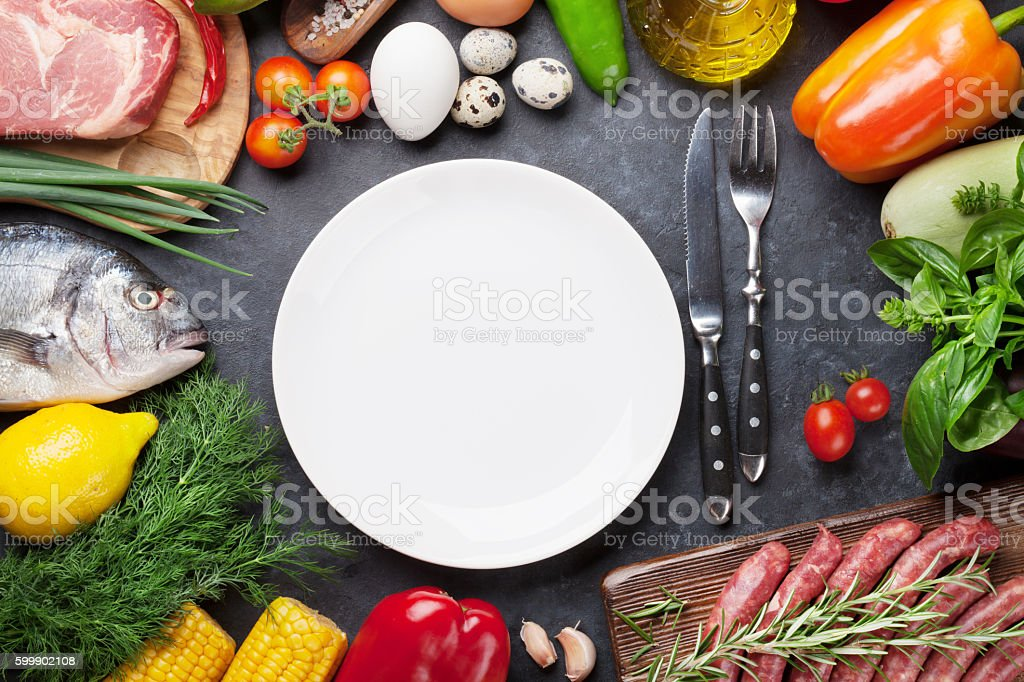 Empty plate surrounded by cooking ingredients stock photo