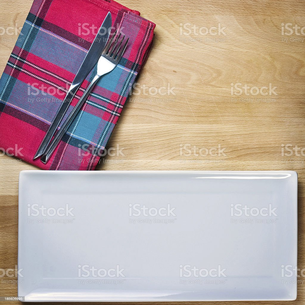 Empty plate with fork and knife on wooden table royalty-free stock photo