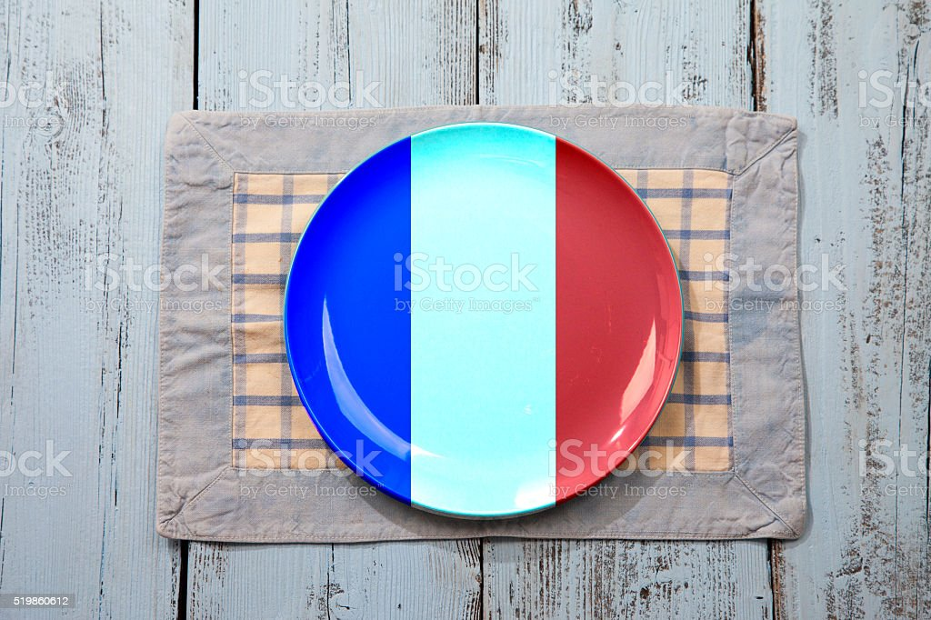 Empty plate with French flag on light blue wooden background stock photo