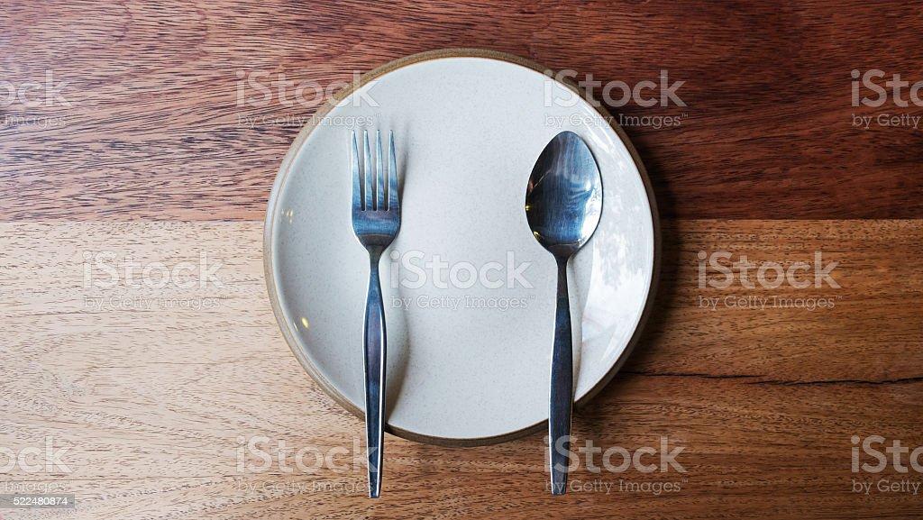 Leere Teller mit Löffel und Gabel auf einem hölzernen Hintergrund. Lizenzfreies stock-foto
