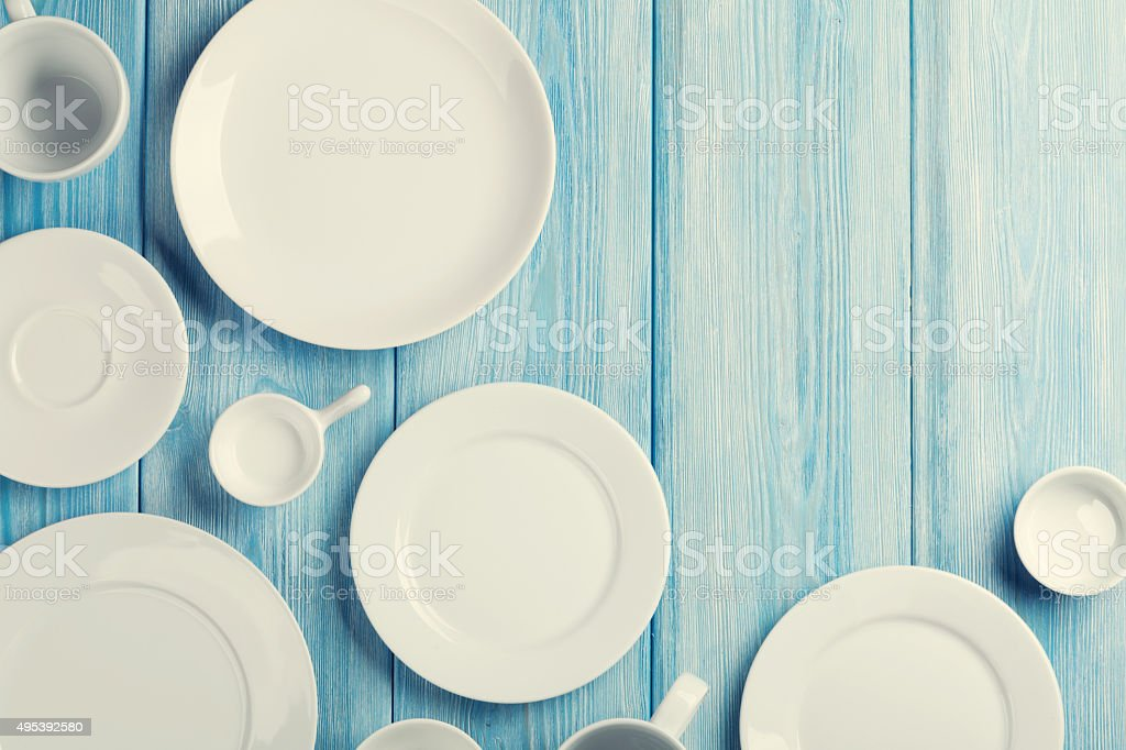 Empty plates and bowls on blue wooden background stock photo