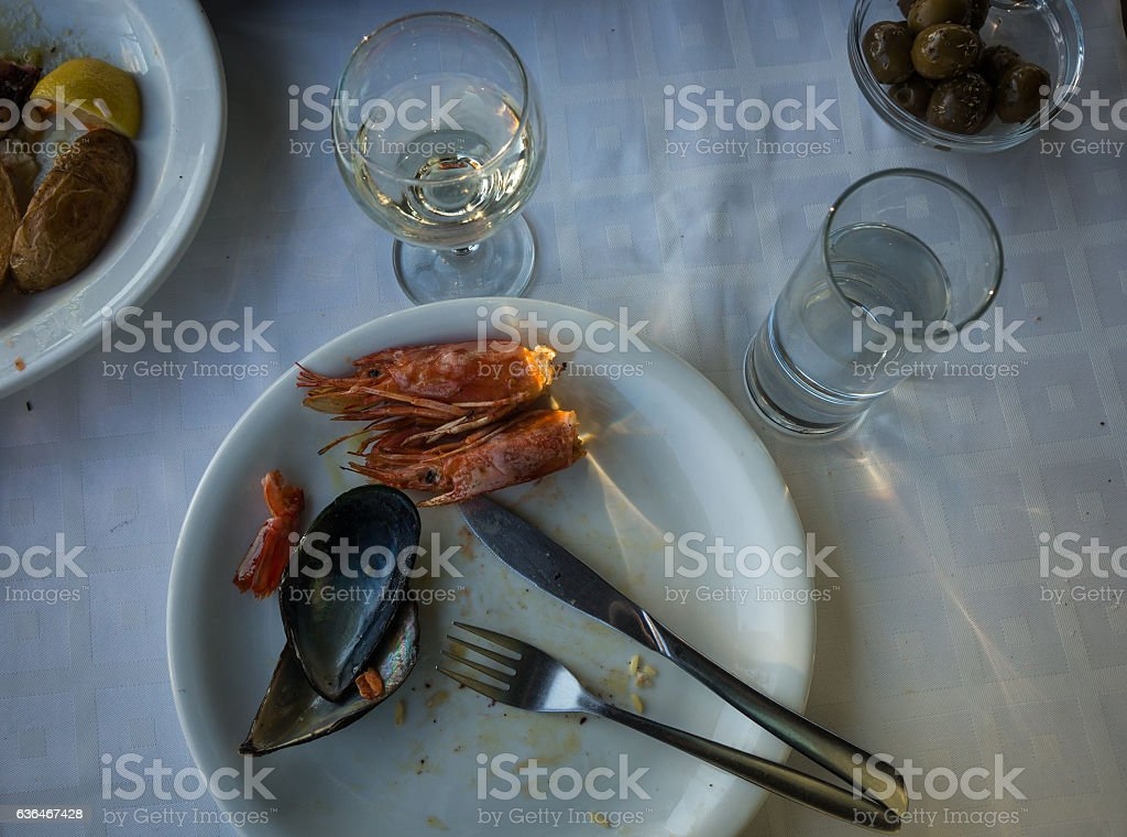 Empty plates with remnants of food after lunch stock photo
