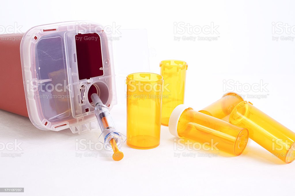 Empty prescription bottles and syringe with disposal container royalty-free stock photo