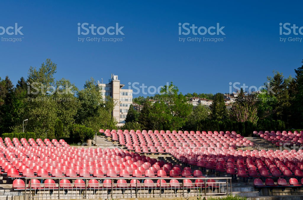Empty red seats in an open space stock photo