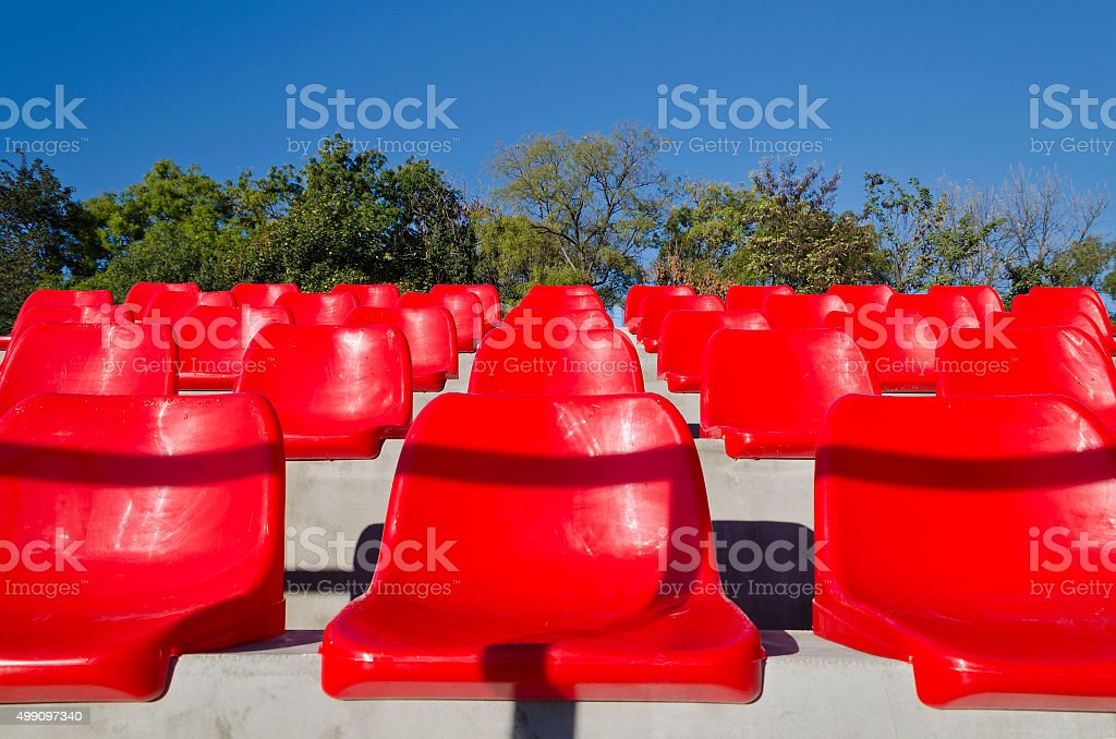Empty red stadium seats in an open space stock photo