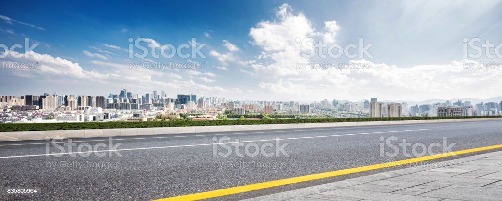 empty road and cityscape of modern city against cloud sky stock photo