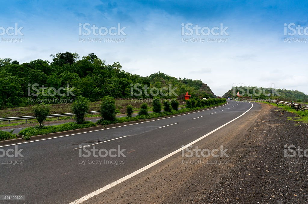 Empty road borded by  hills with cloudy skies stock photo