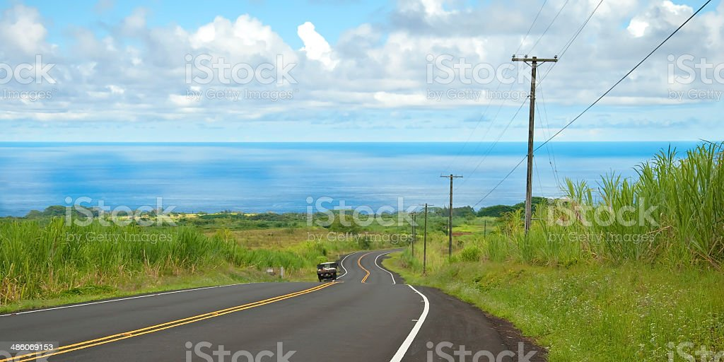 Empty road in Hawaiian countryside with car and ocean royalty-free stock photo