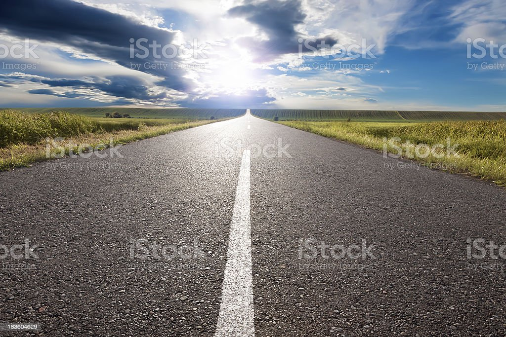 Empty road leading towards the sun stock photo