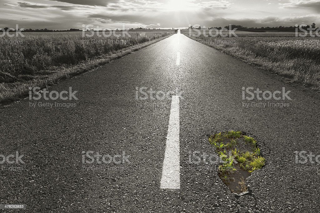 Empty road with a hole towards the setting sun royalty-free stock photo