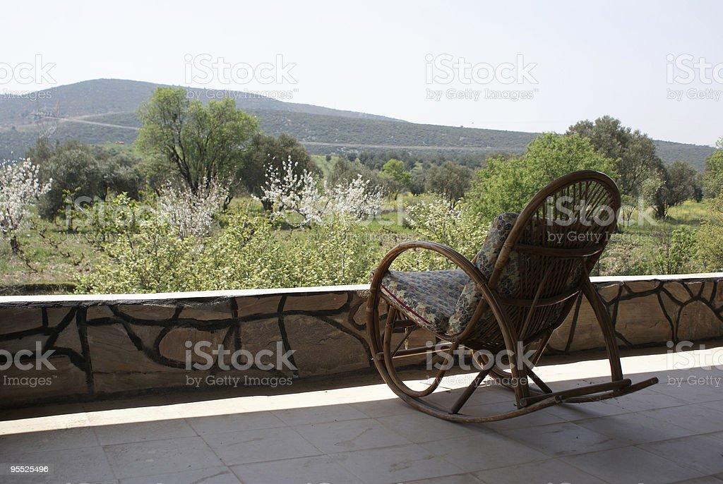 Empty rocking chair near grassy field royalty-free stock photo