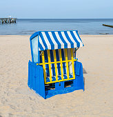 Empty roofed wicker beach chair with sea and sky