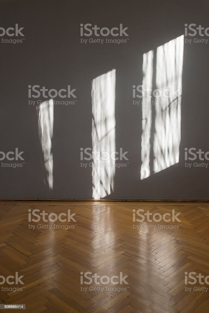 Empty room with window shadows on wall stock photo
