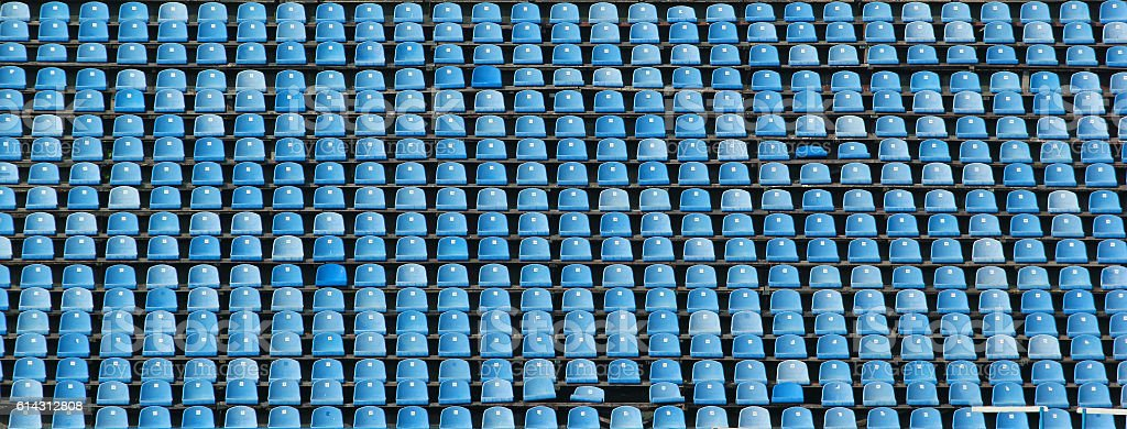 Empty rows of blue stadium seats stock photo