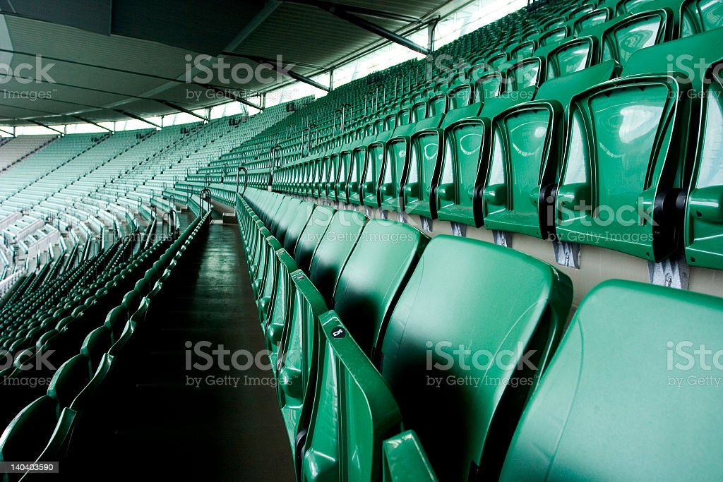 Empty rows of green seats in an outdoor stadium royalty-free stock photo