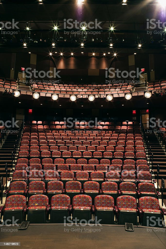 Empty rows of seats in a theater with house lights on stock photo