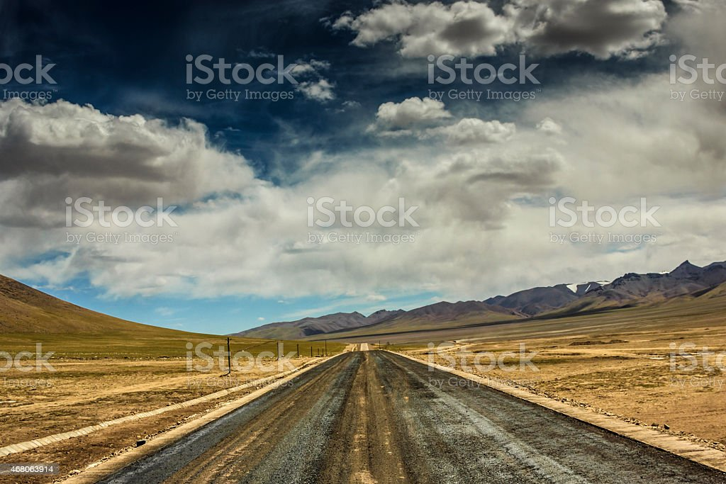 Empty rural road going through desert under cloudy sky stock photo
