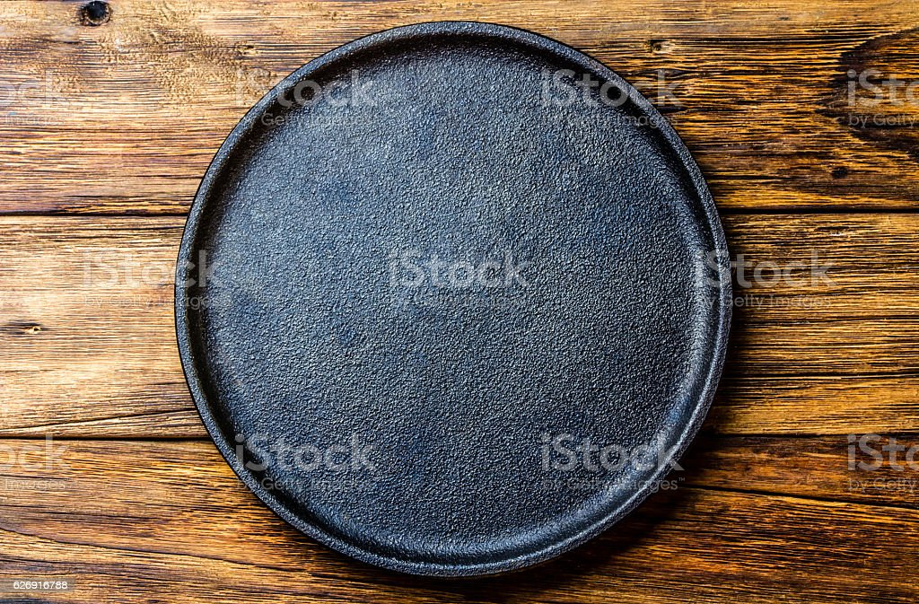 Empty rustic black cast iron plate over old wooden background stock photo