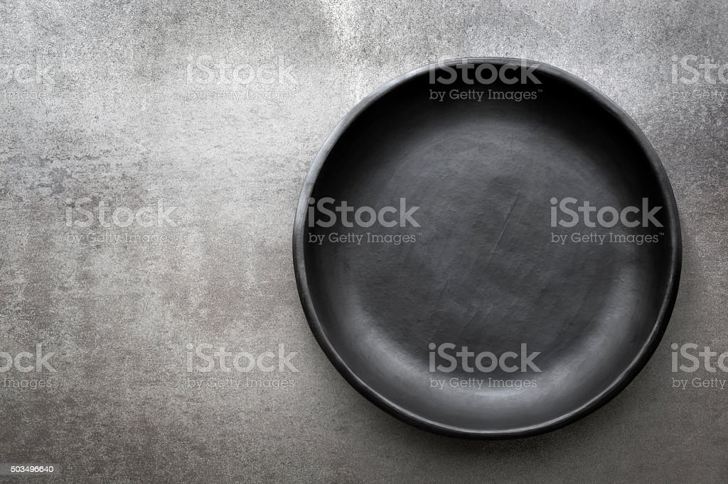 Empty Rustic Black Plate over Slate stock photo