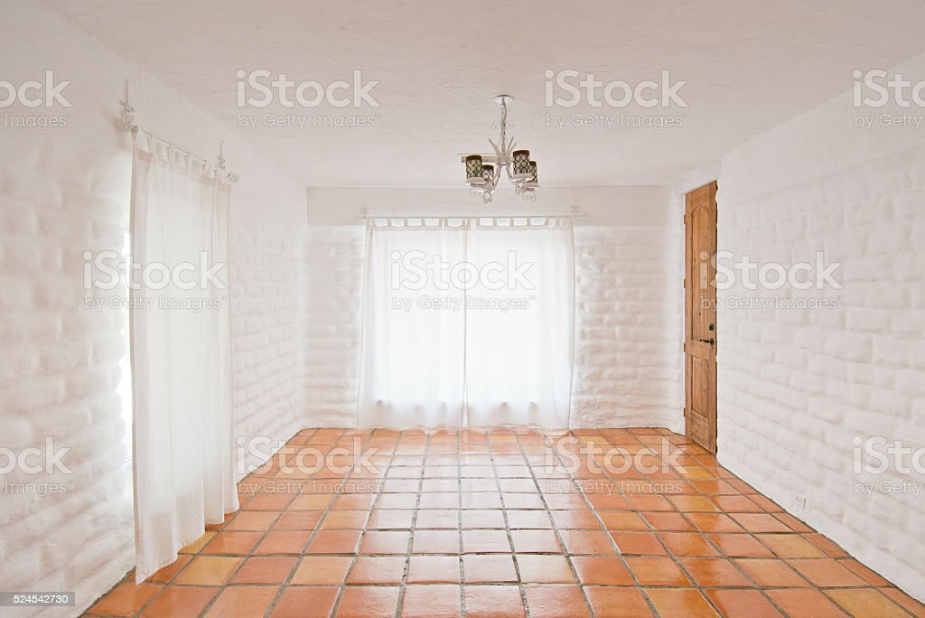 Empty Rustic Room with White Adobe Brick Wall and Tiles stock photo