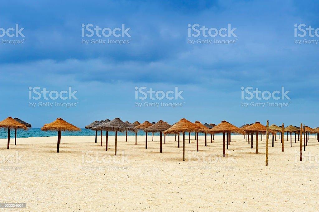 Empty sandy beach with parasols , Algarve,Portugal stock photo