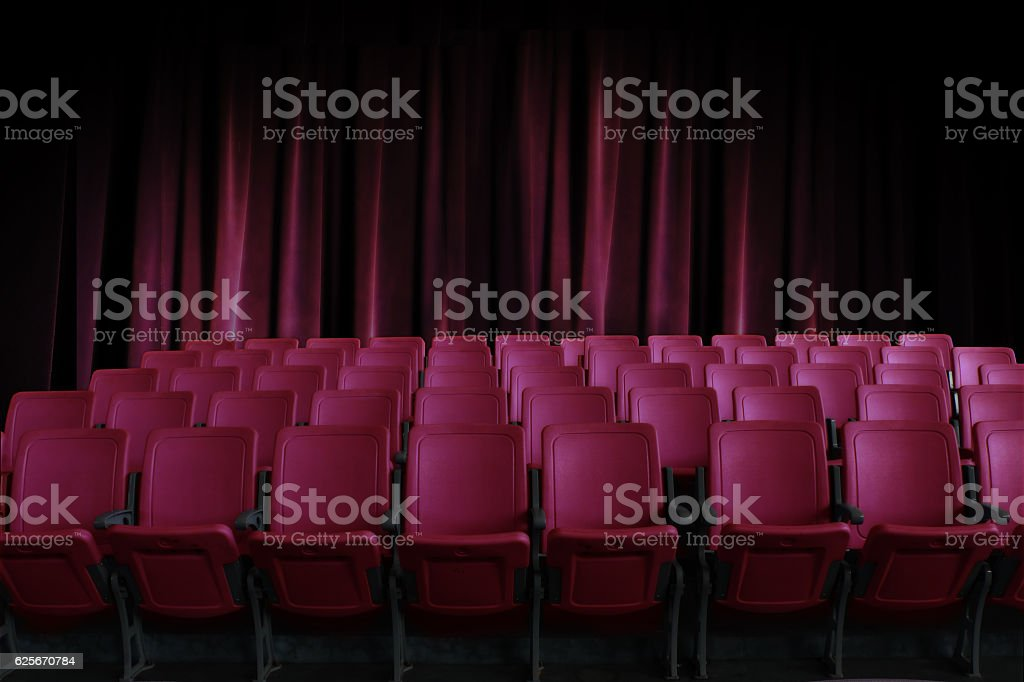 empty seats in the cinema with old red curtain background stock photo