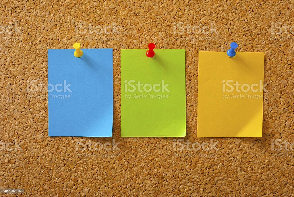 A empty set of three sticky notes pinned up on a board stock photo