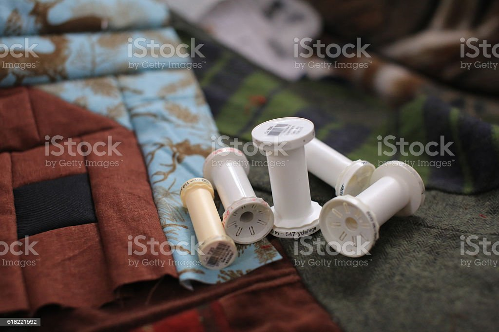 Empty Sewing Thread Spools on Cozy Quilt Squares stock photo