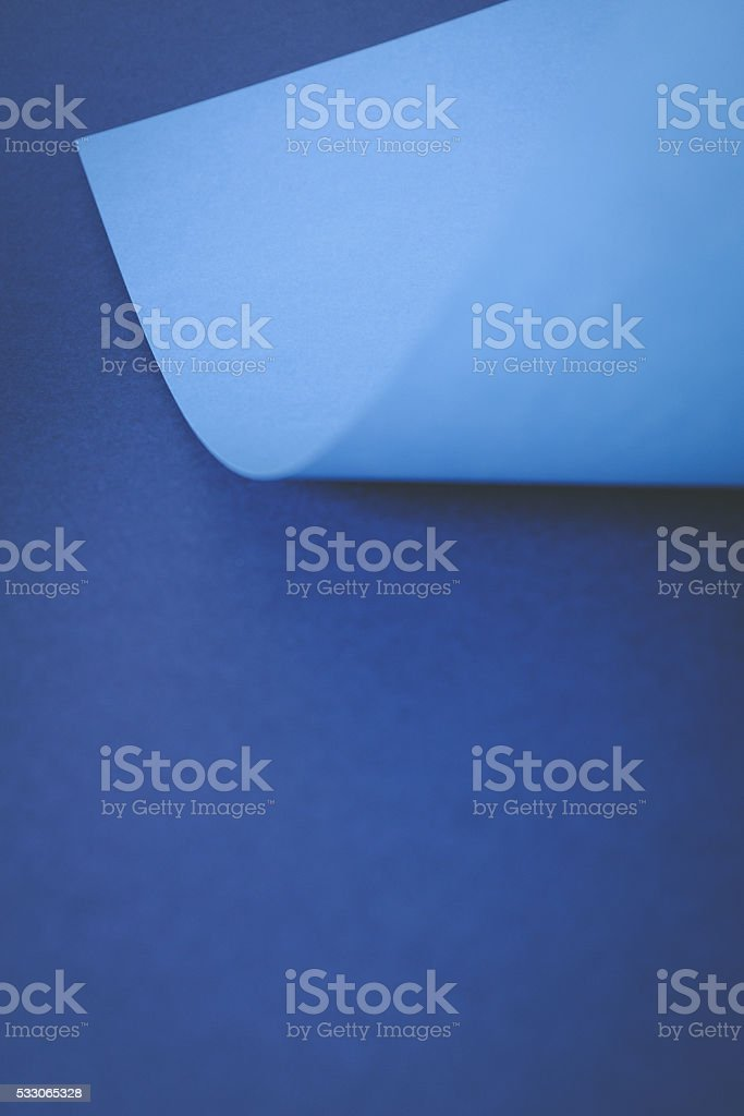 empty sheet of blue paper with curled corner. stock photo