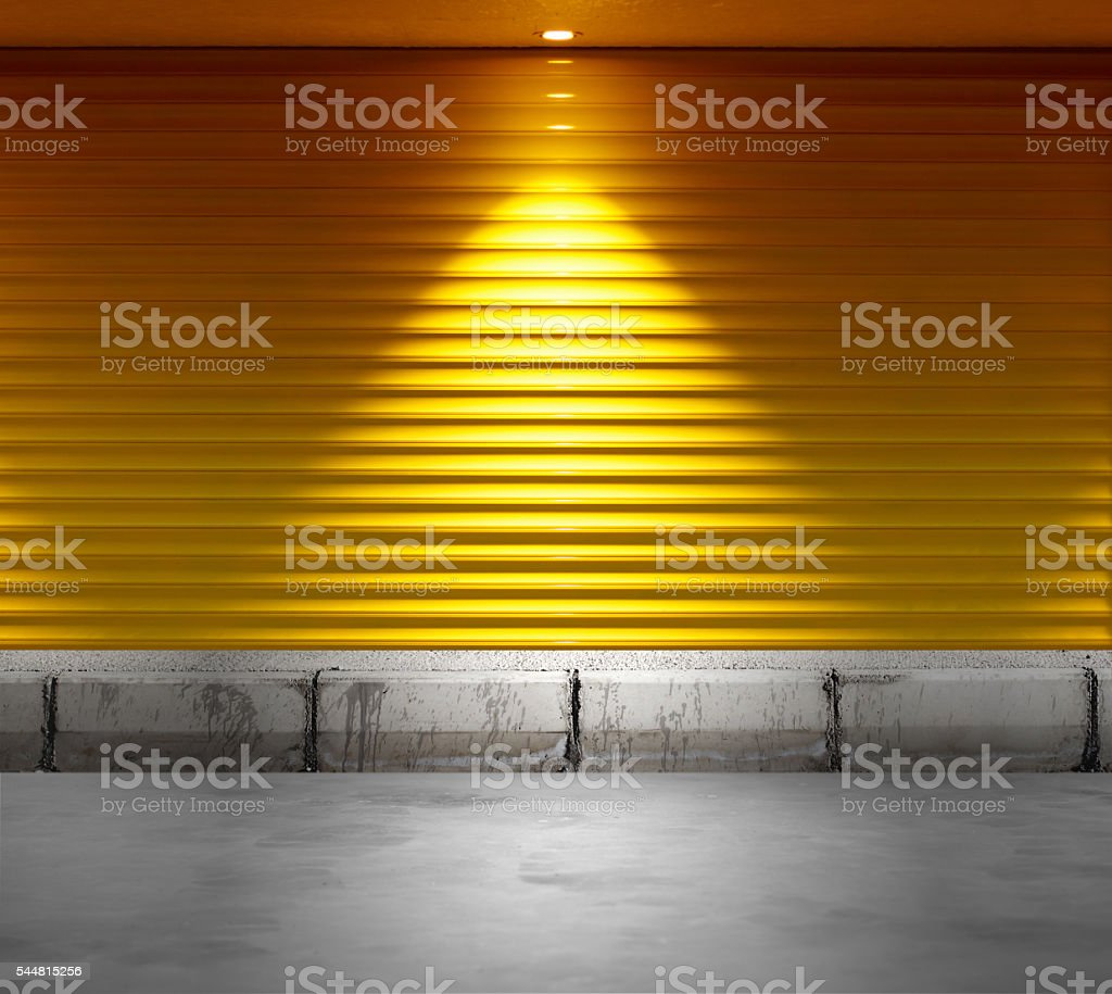 Empty shop with metallic roller shutter yellow door stock photo