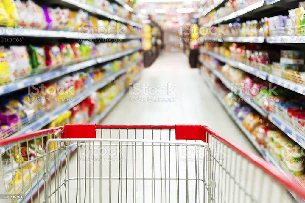 Empty shopping cart in a supermarket aisle stock photo