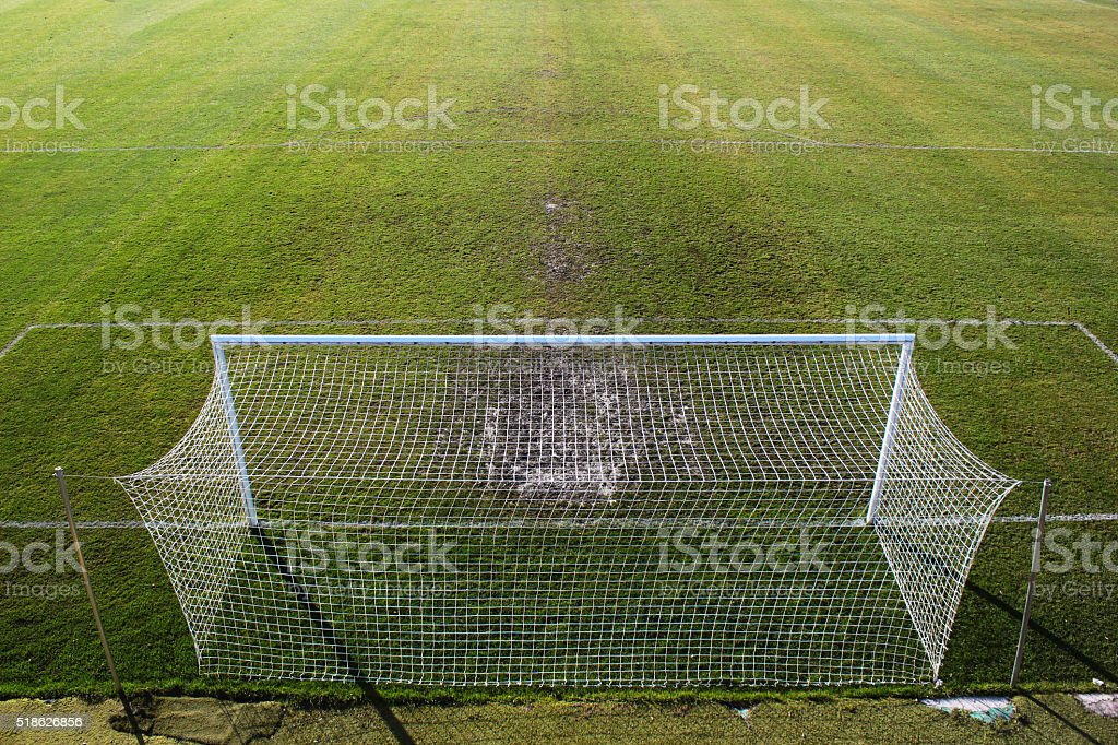 Empty soccer field and trampled grass near the gate. stock photo