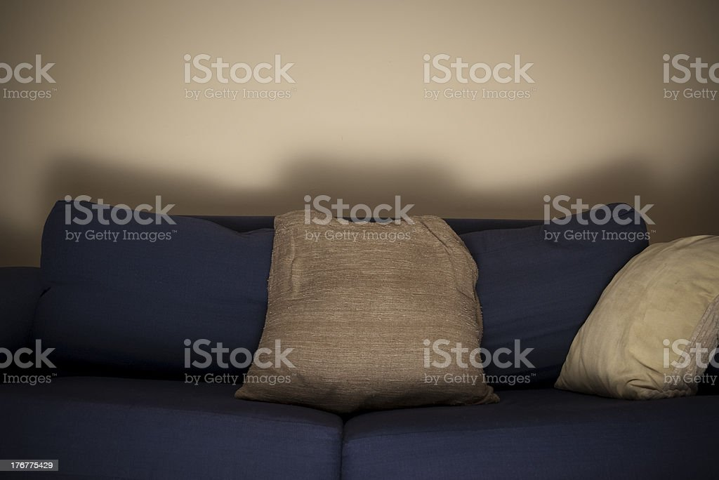 Empty sofa lit by a TV stock photo