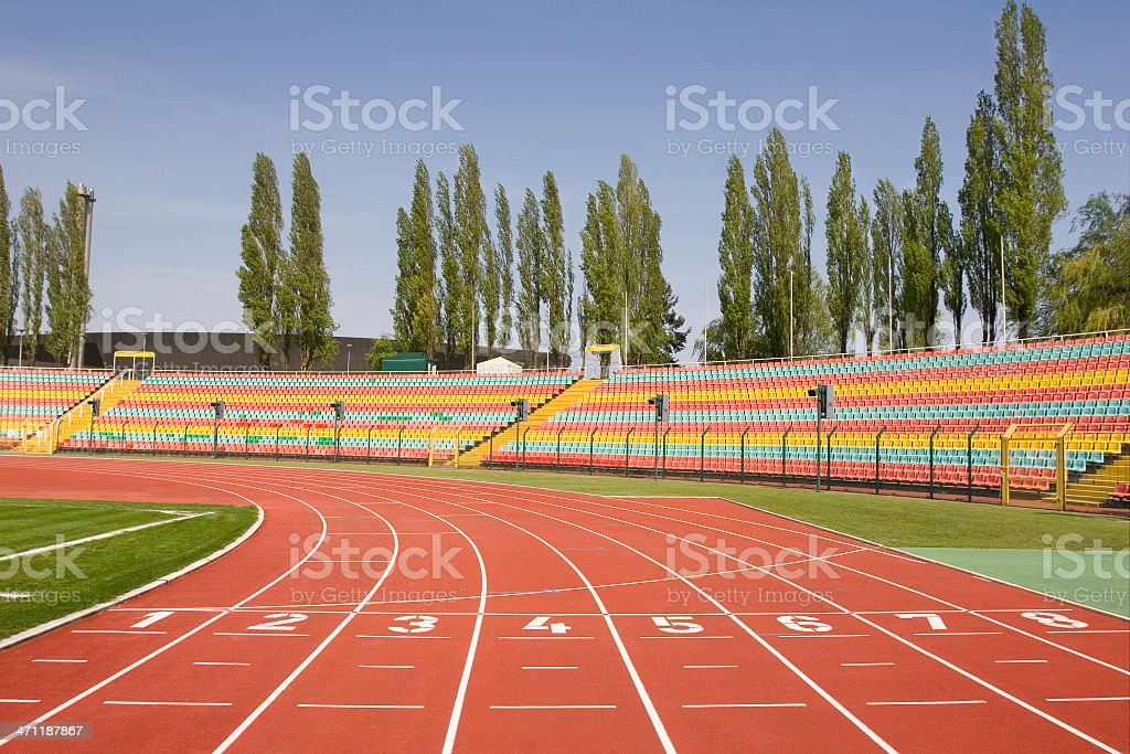Empty Sport Stadium With Running Lanes and Colourful Bleachers stock photo