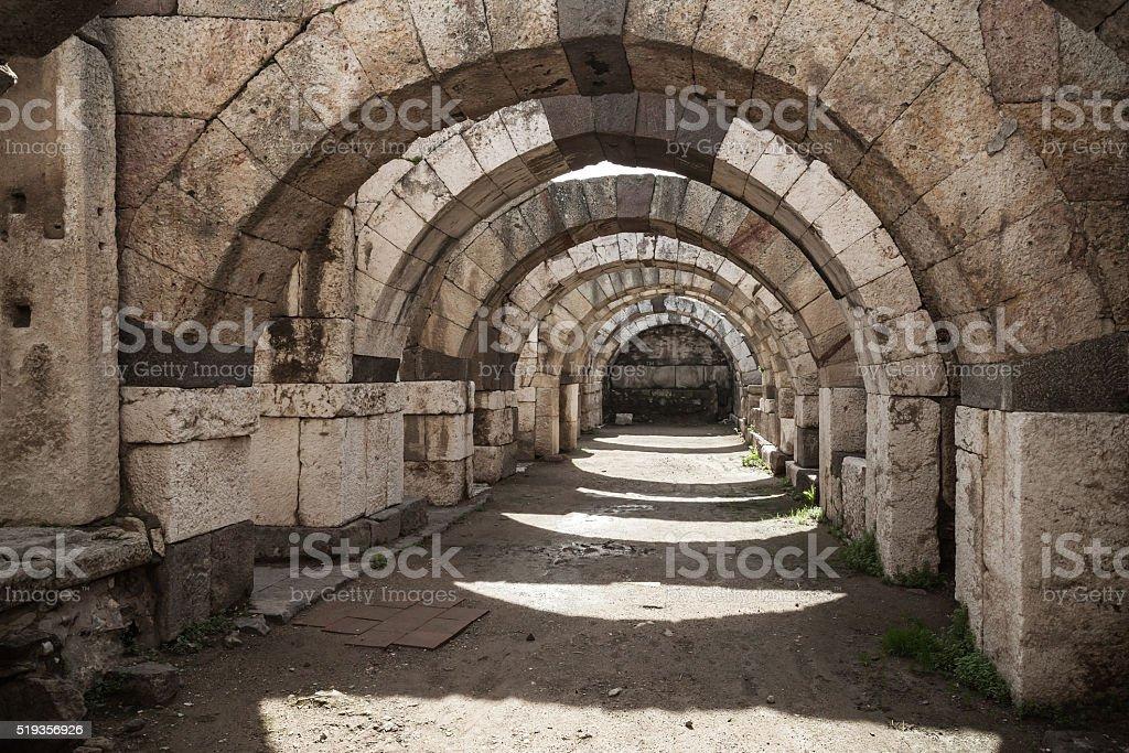 Empty stone corridor with arcs and columns stock photo