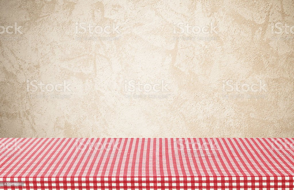 Empty table covered with red checked tablecloth over cement wall stock photo