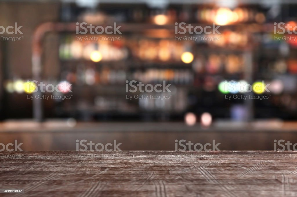 Empty table edge in a pub bar, defocused background stock photo