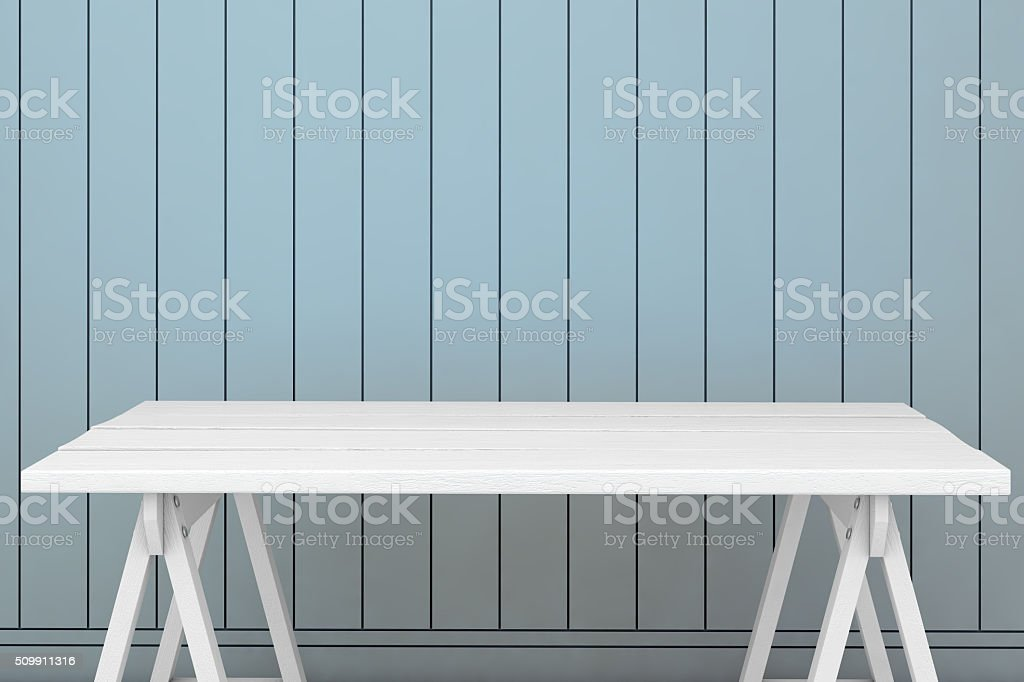 Empty table surrounded by the light blue wall stock photo