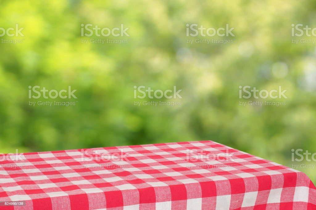 Empty table with a red checkered cloth. Green blurred background. stock photo