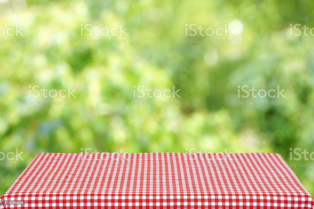 Empty table with a red checkered cloth in the summer garden. Blurred background. stock photo