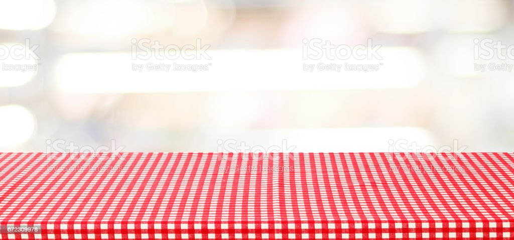 Empty table with red check tablecloth over blurred store with bokeh...