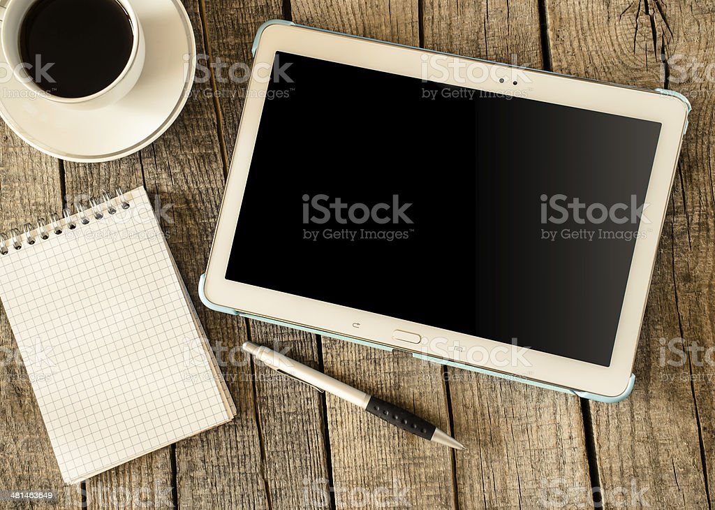 Empty tablet pc and a coffee and notebook with pen stock photo