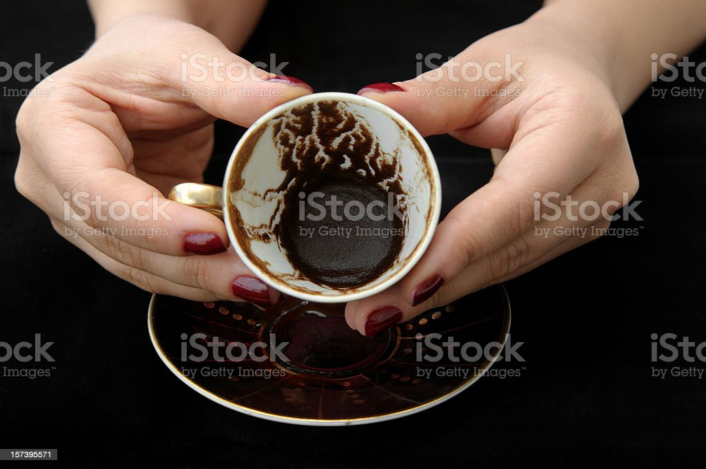 Empty tea cup held to show the dregs by fortune teller stock photo