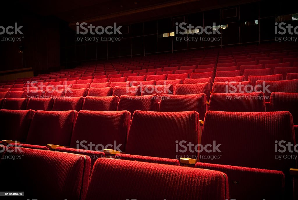Empty theatre with red seats in low light stock photo