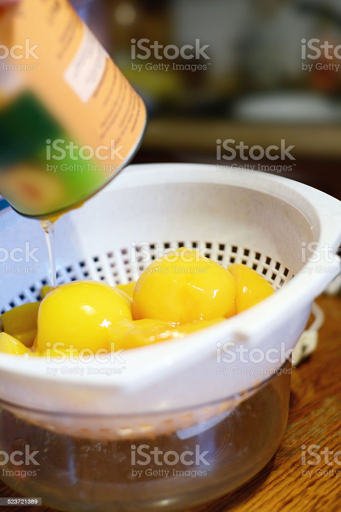 empty tin can with peach in a bowl stock photo